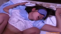 A young Asian girl wearing a blindfold is laying on